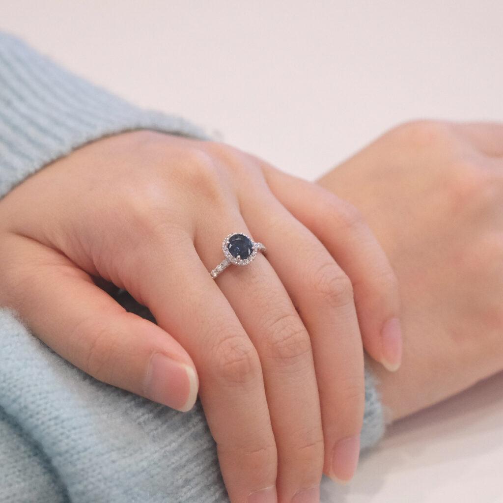 Blue sapphire gemstone with halo diamond engagement ring on hand