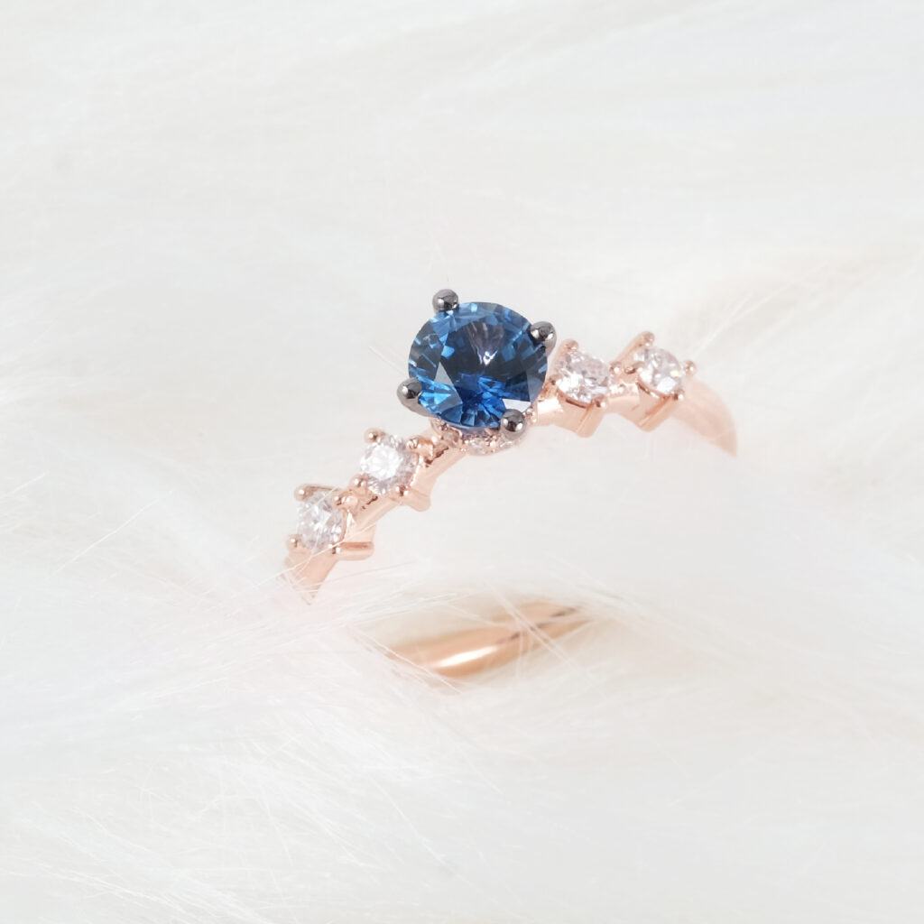round blue sapphire with side diamonds ring